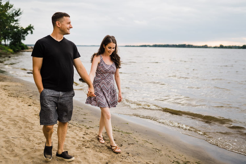 Couple walk hand in hand along beach