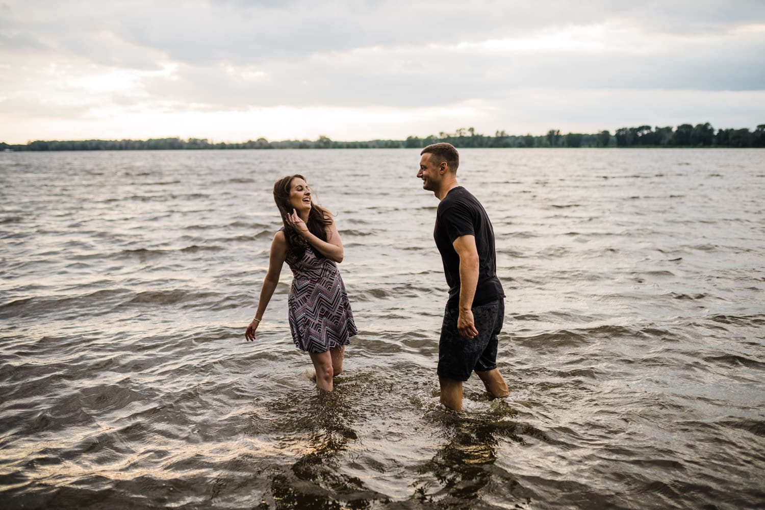couple playfully splashes water at one another - Petrie Island Engagement Ottawa Beach Engagement