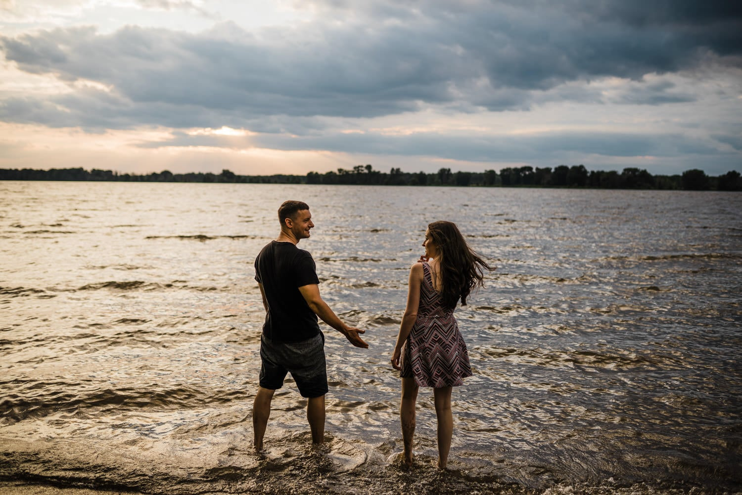 couple walk out into the water at sunset - Petrie Island Ottawa Beach Engagement