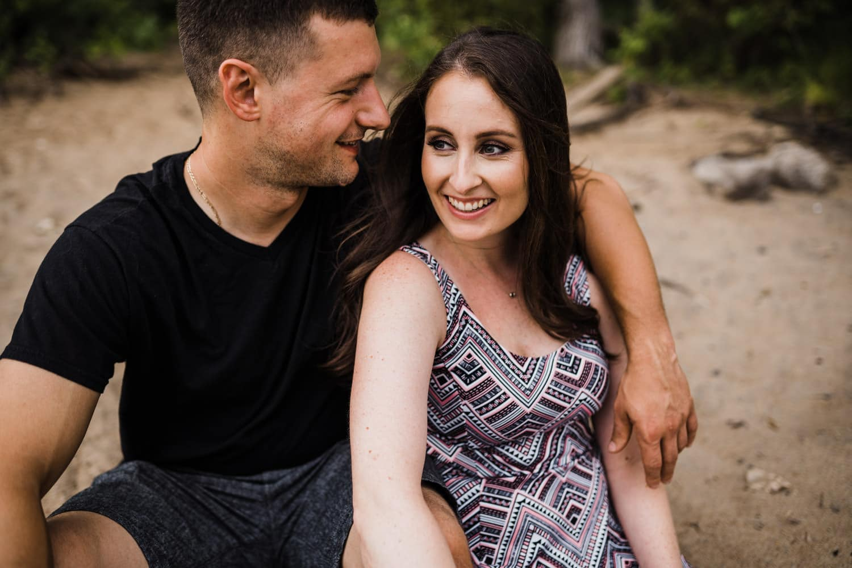 couple sit together on sandy beach - Petrie Island Ottawa Beach Engagement