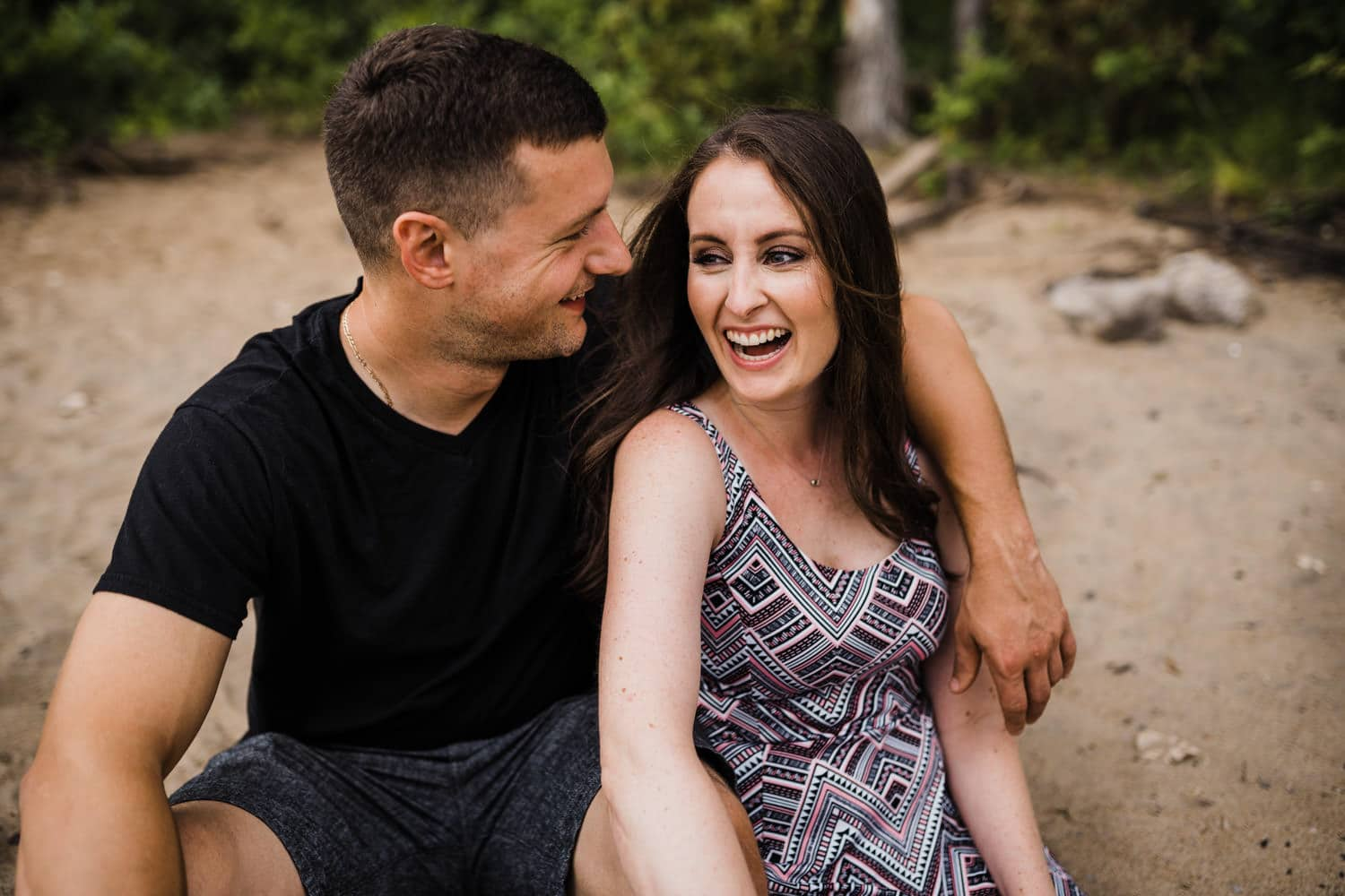 couple laugh together on the beach - Petrie Island Ottawa Beach Engagement