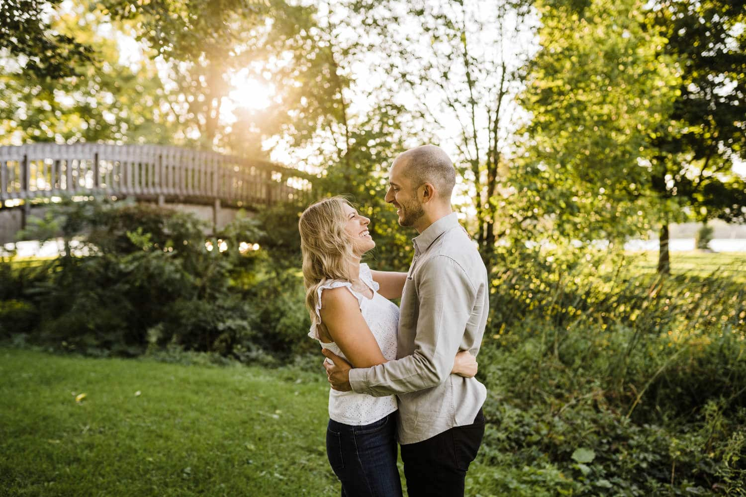 couple laugh together during summer engagement session