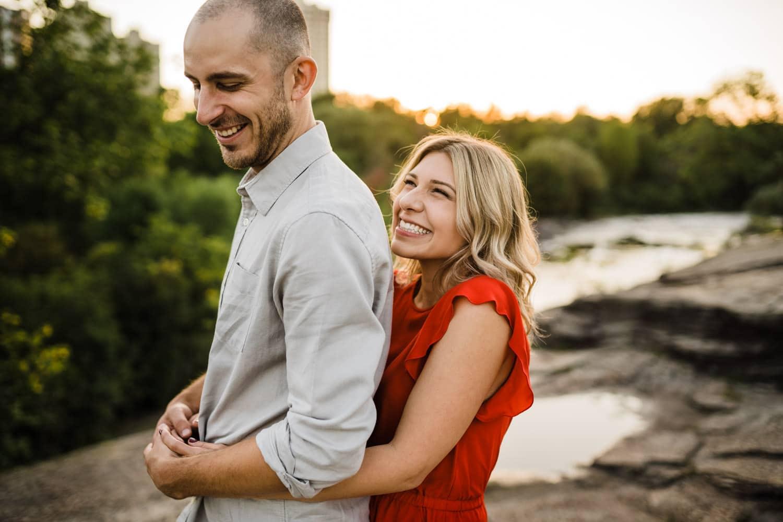 woman hugs man from behind and giggles - carley teresa photography