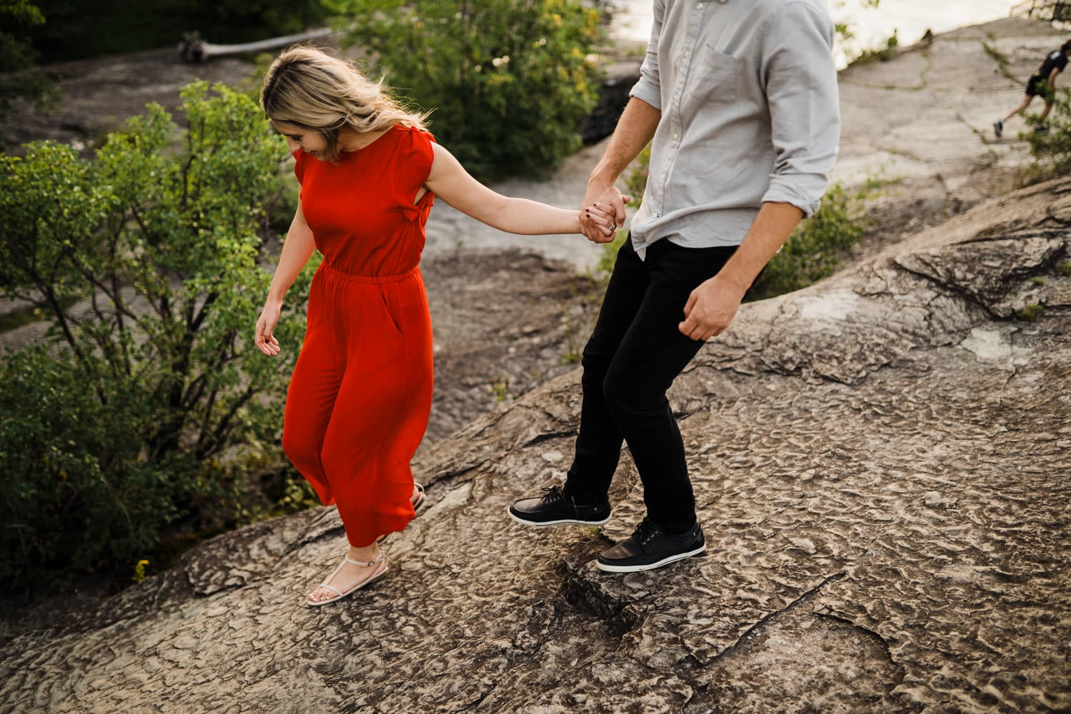 couple hold hands and walk down rocks together