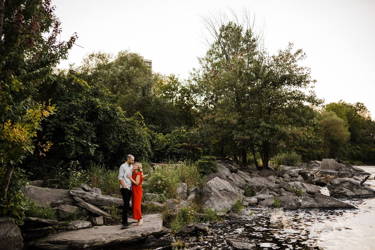 couple stand on rocks by the water together - hogs back engagement session