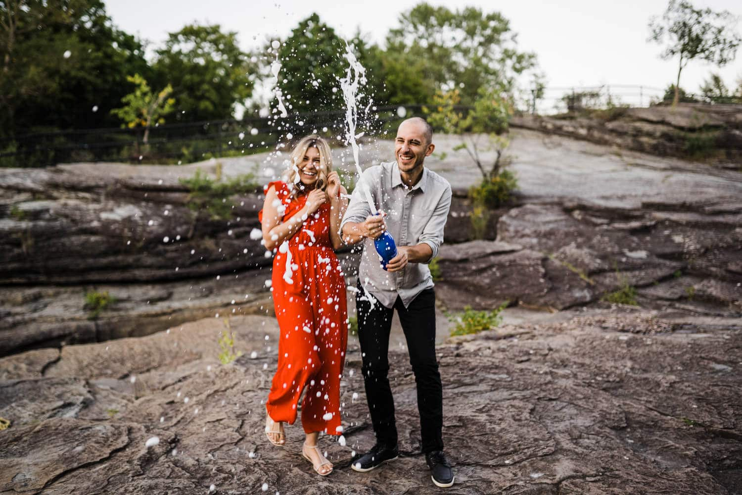 couple pop champagne together - hogs back engagement session
