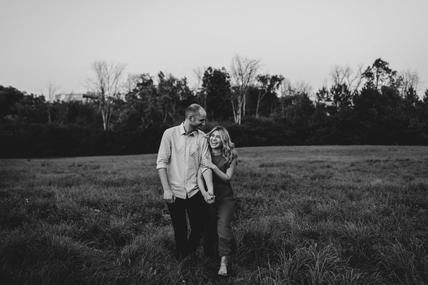 couple walk through open field together and laugh - carley teresa photography