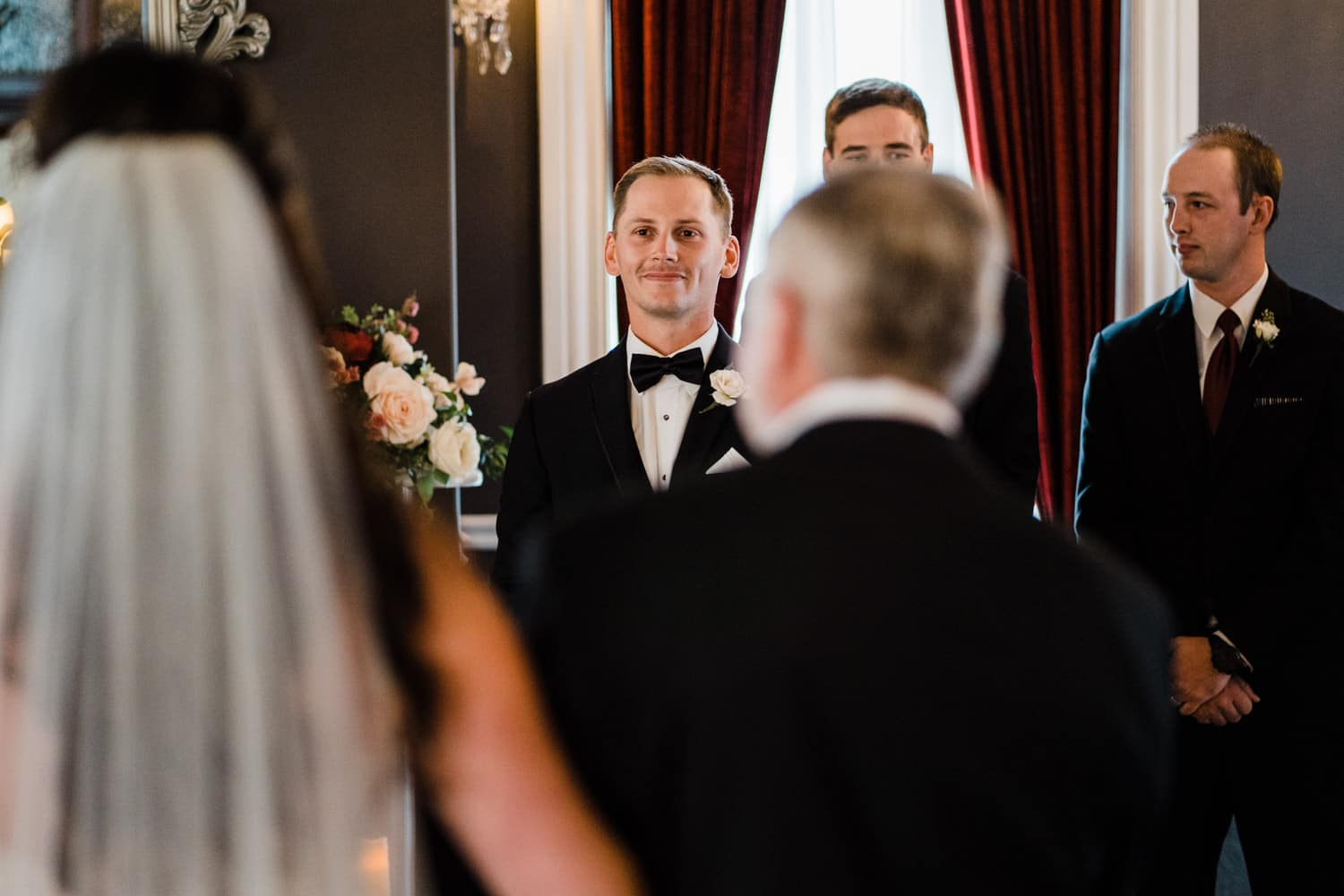 groom watches his bride come down the aisle