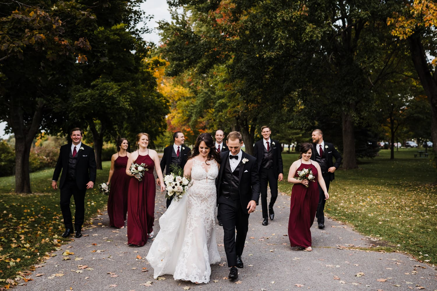 wedding party walks in a park together - the grand hotel wedding