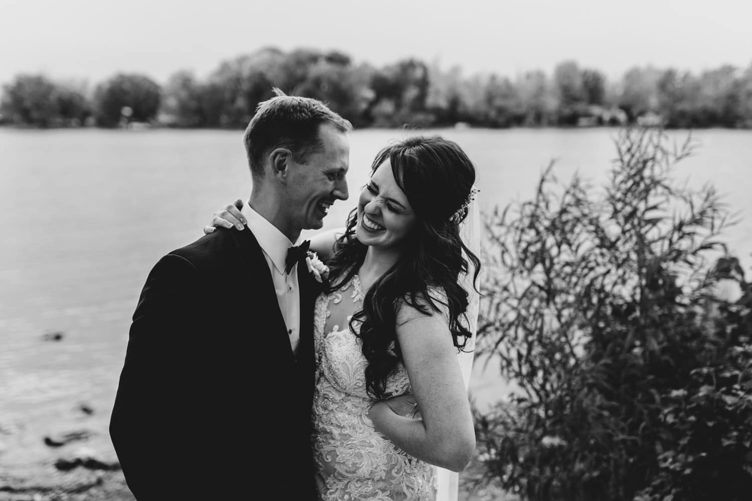 bride and groom laugh together at water's edge