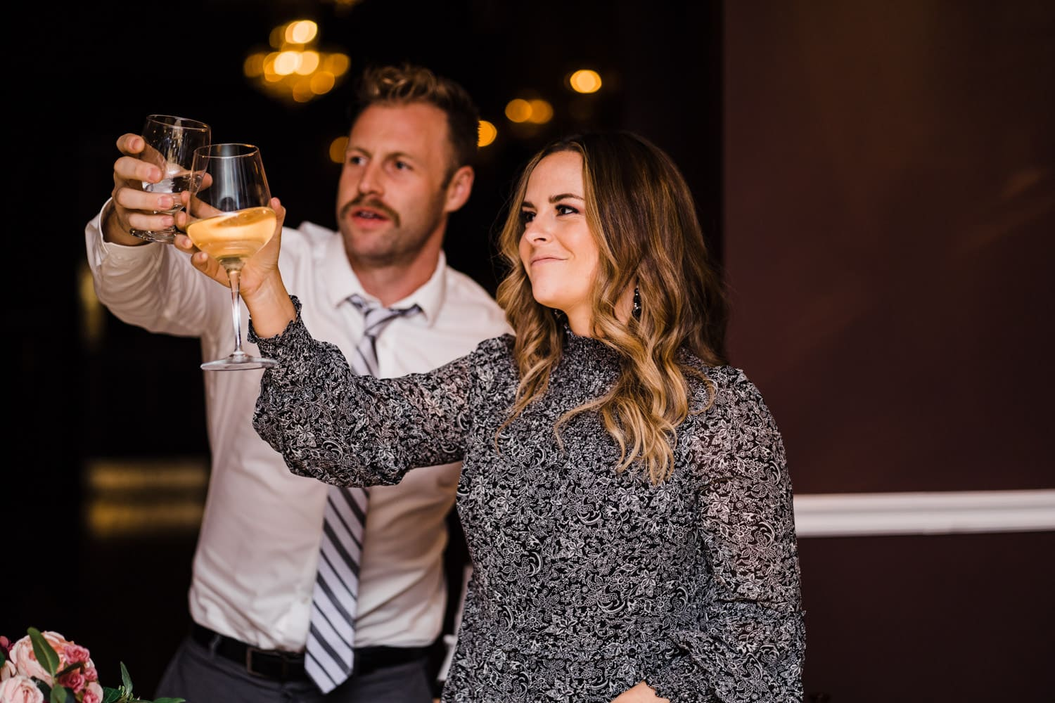 guests raise their glasses for a toast during wedding reception