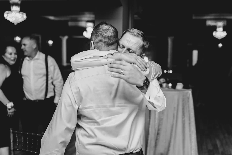 groom emotionally hugs friend during reception