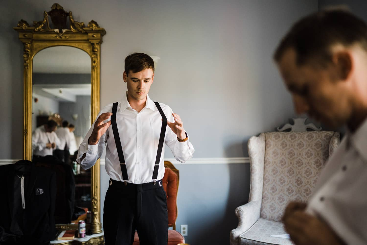 groomsmen plays with suspenders while getting ready