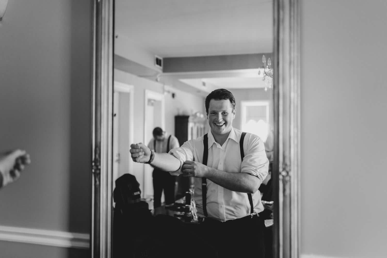 groomsmen looks in the mirror as he gets ready