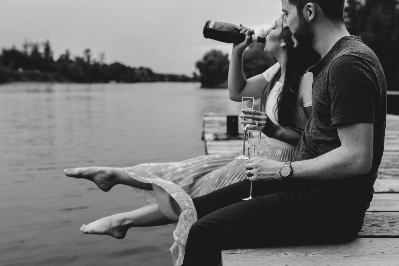 couple sits on dock and drink champagne