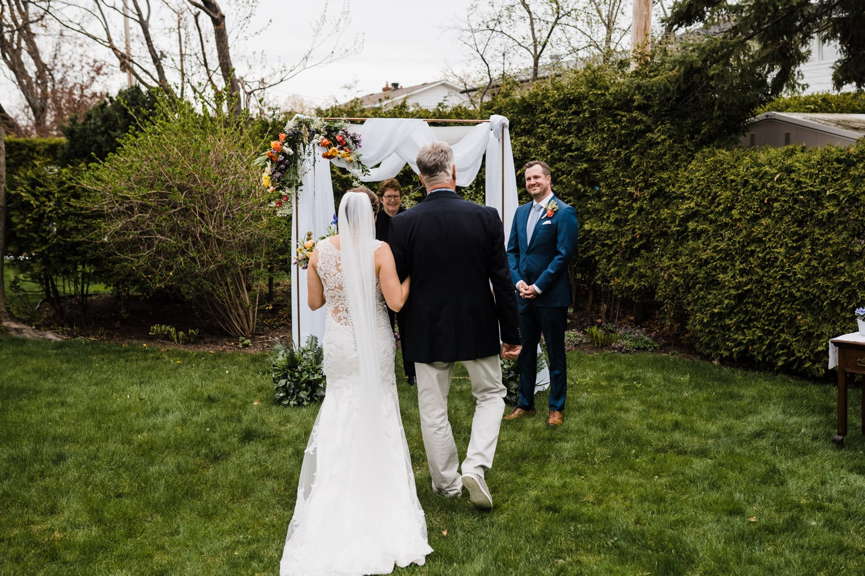 groom looks on as bride walks down the aisle - small backyard wedding