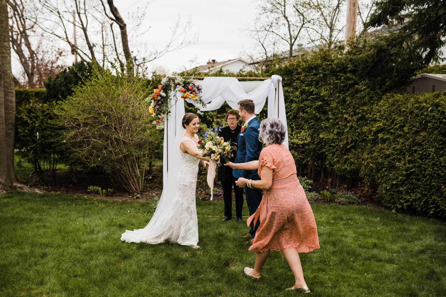 mother of the bride steps in to take bouquet from bride