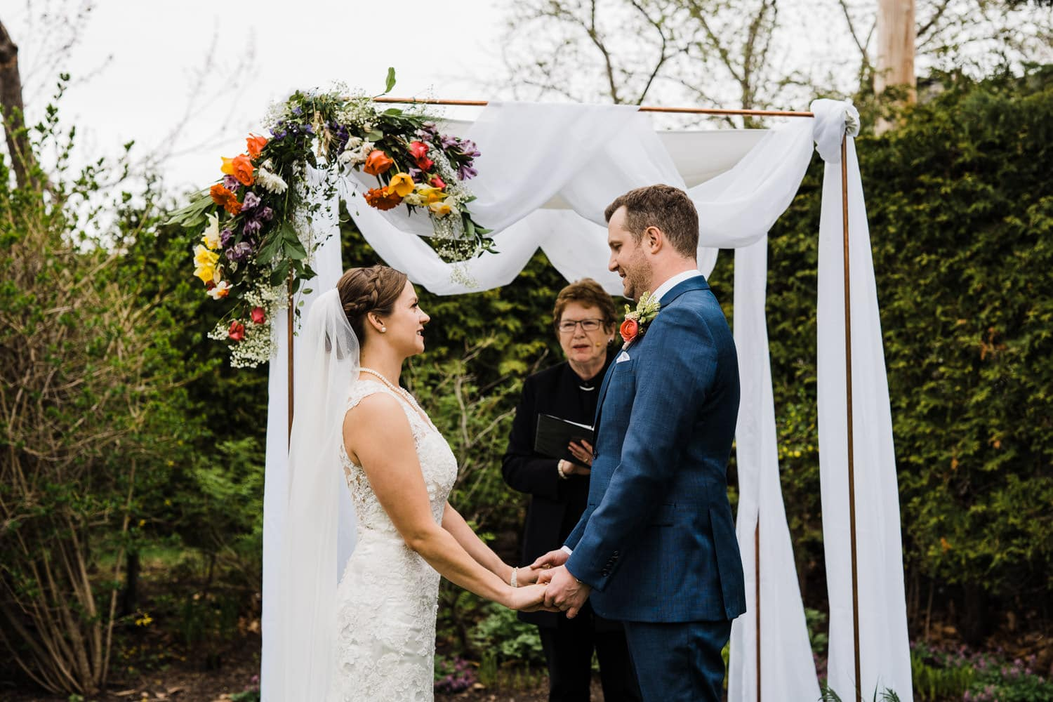 bride and groom hold hands during intimate wedding ceremony - small backyard wedding ottawa