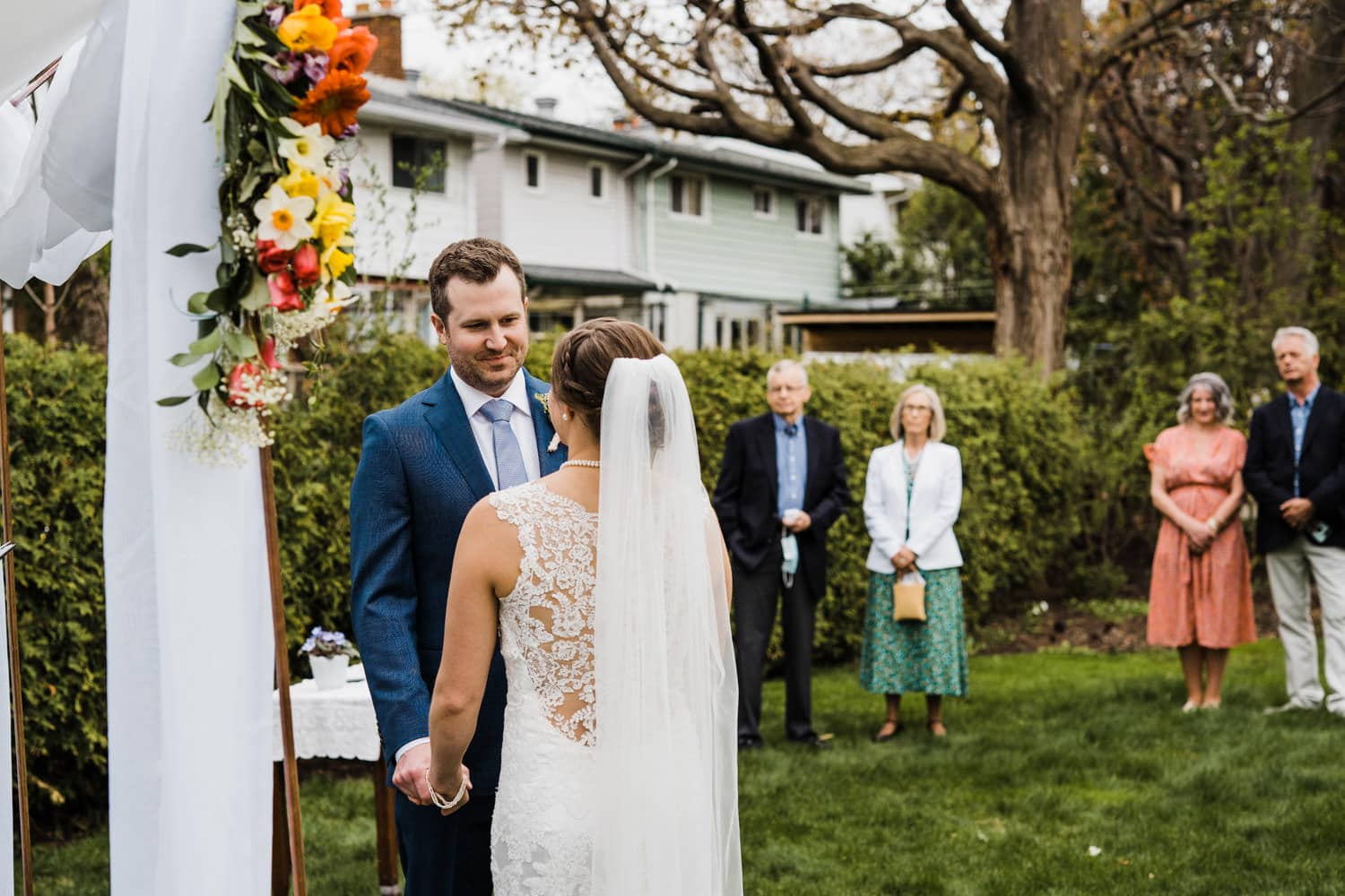 groom looks at his wife during intimate backyard ceremony