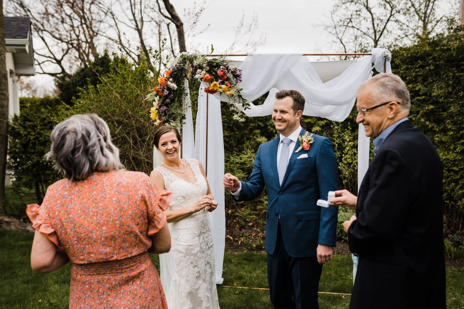 couple laughs as they get ready to exchange rings - intimate backyard ceremony