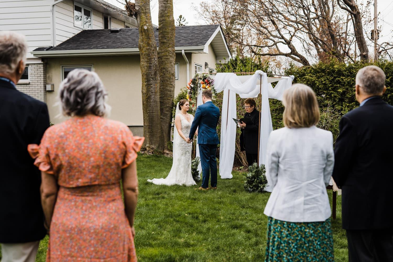 parents look on during intimate backyard ceremony - small backyard wedding ottawa