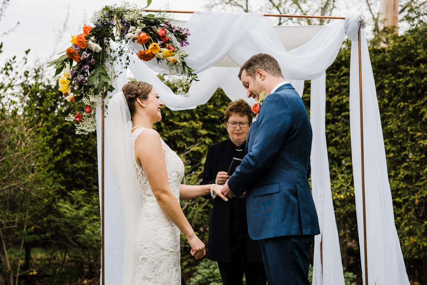 couple laughs as they exchange rings - intimate backyard ceremony