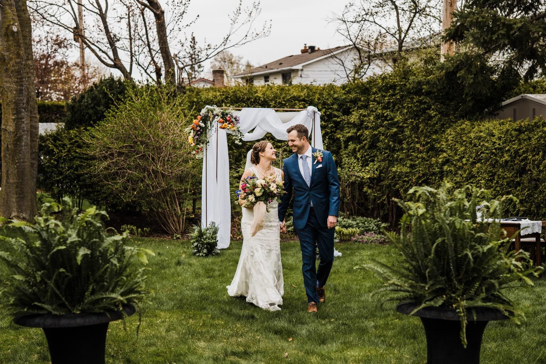 couple walk down aisle after intimate backyard ceremony - small backyard wedding ottawa