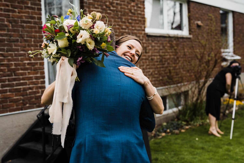couple hug after intimate backyard ceremony