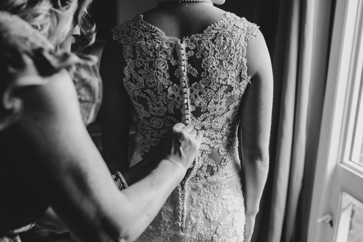 mother of the bride does up the buttons on bride's dress