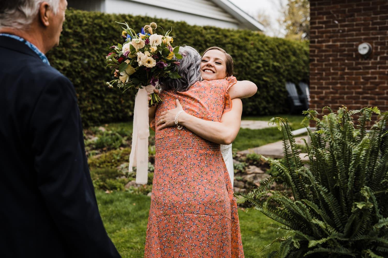 bride hugs her mom after intimate backyard ceremony - small backyard wedding ottawa