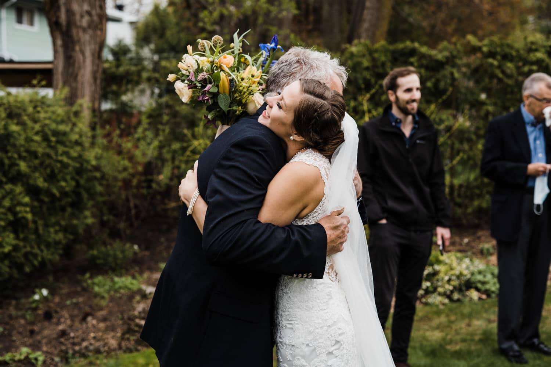 bride hugs her dad after intimate backyard ceremony