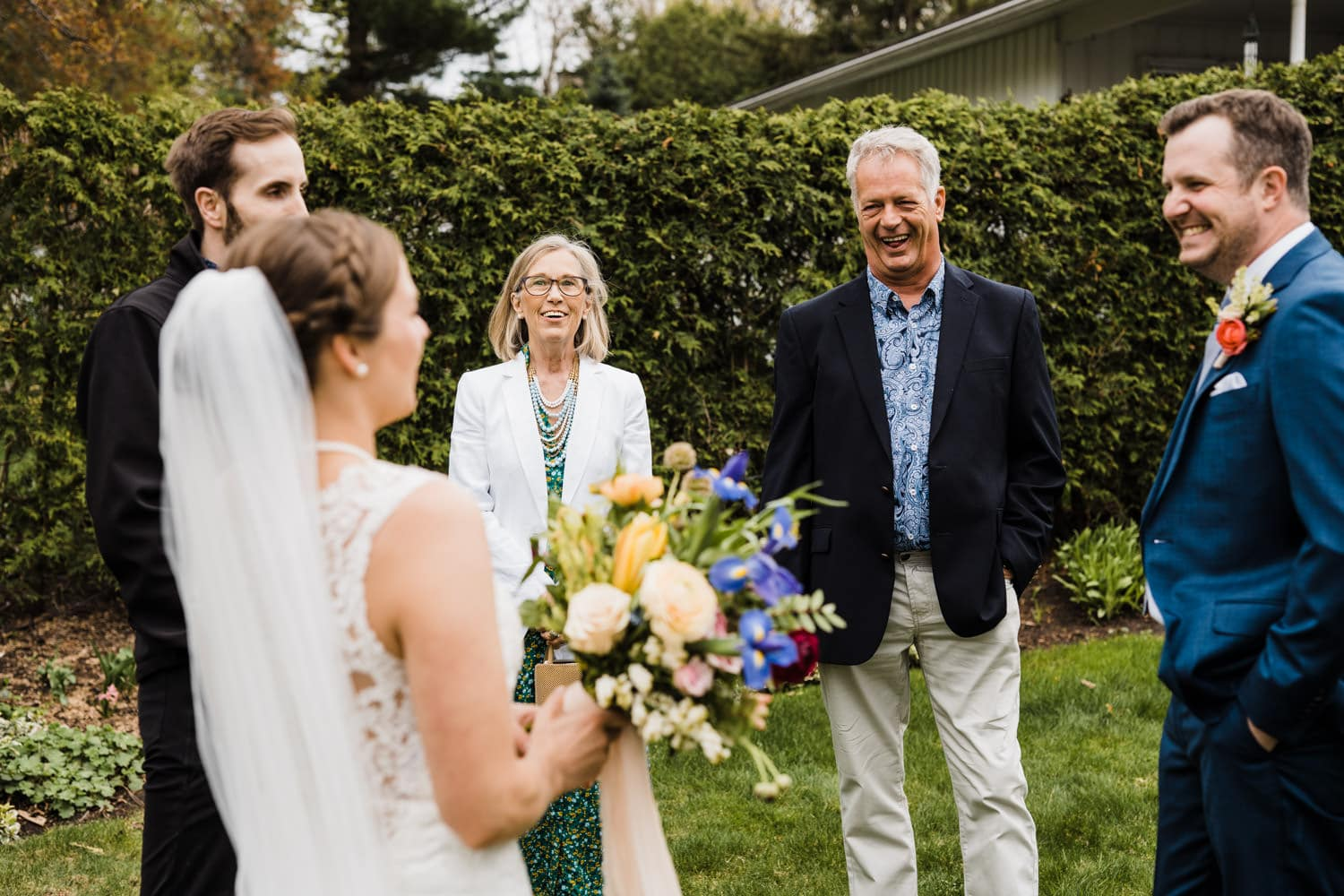 family laughs together after intimate backyard ceremony
