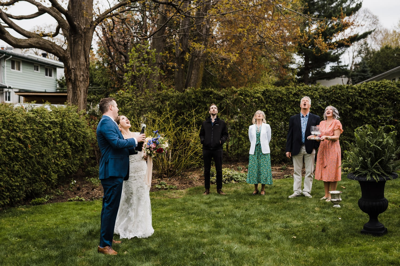 couple pops champagne after small backyard wedding ottawa
