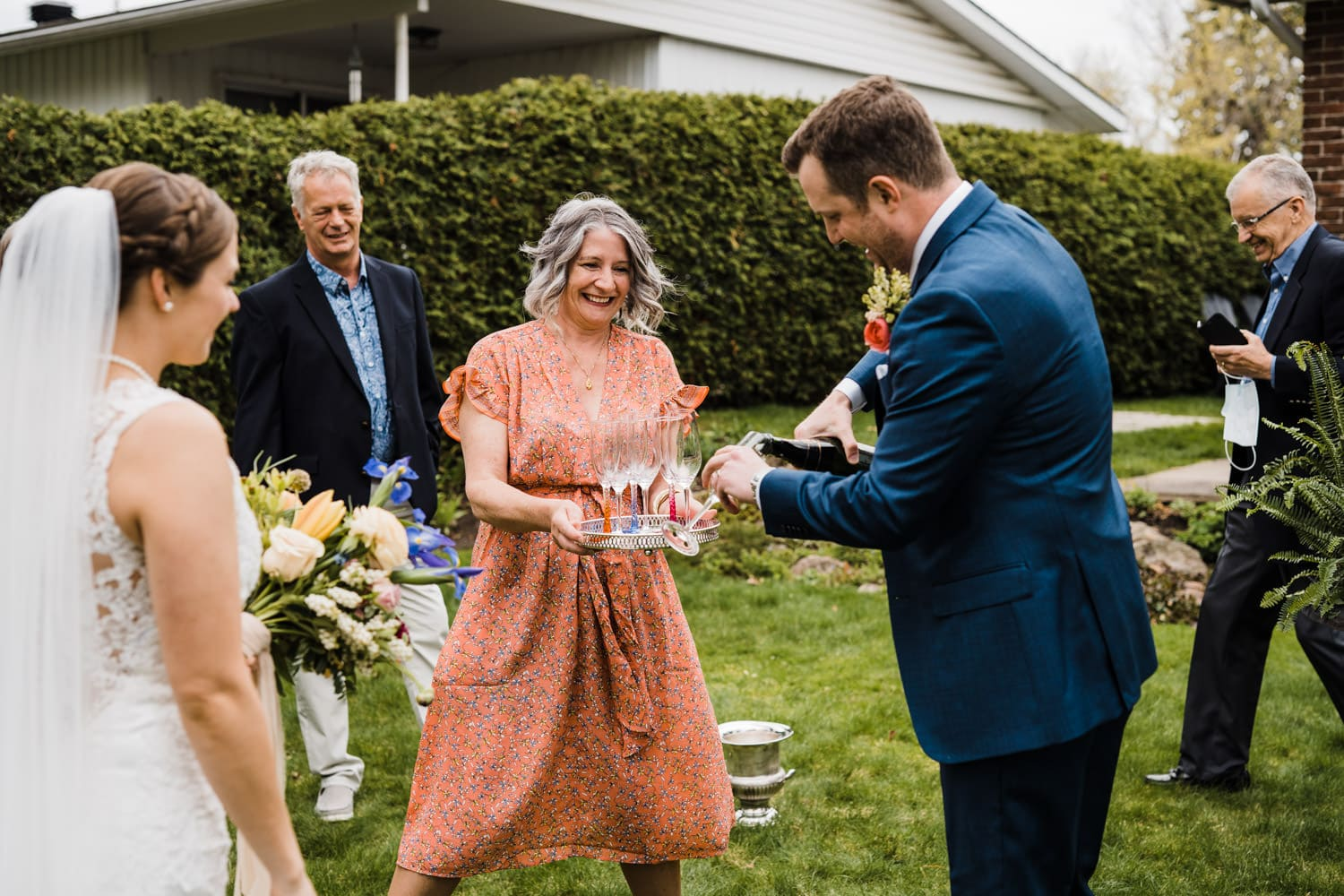 couple pours champagne to celebrate intimate backyard ceremony
