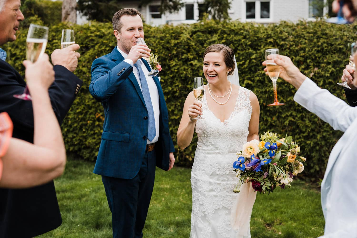 couple cheers with champagne during small backyard wedding ottawa