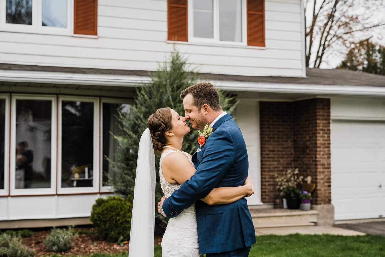 couple hug infront of their home - small backyard wedding ottawa