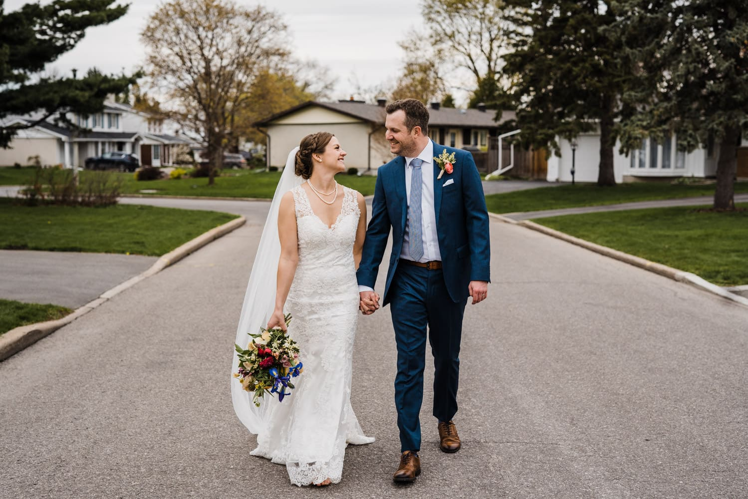 couple walk hand in hand after intimate backyard ceremony