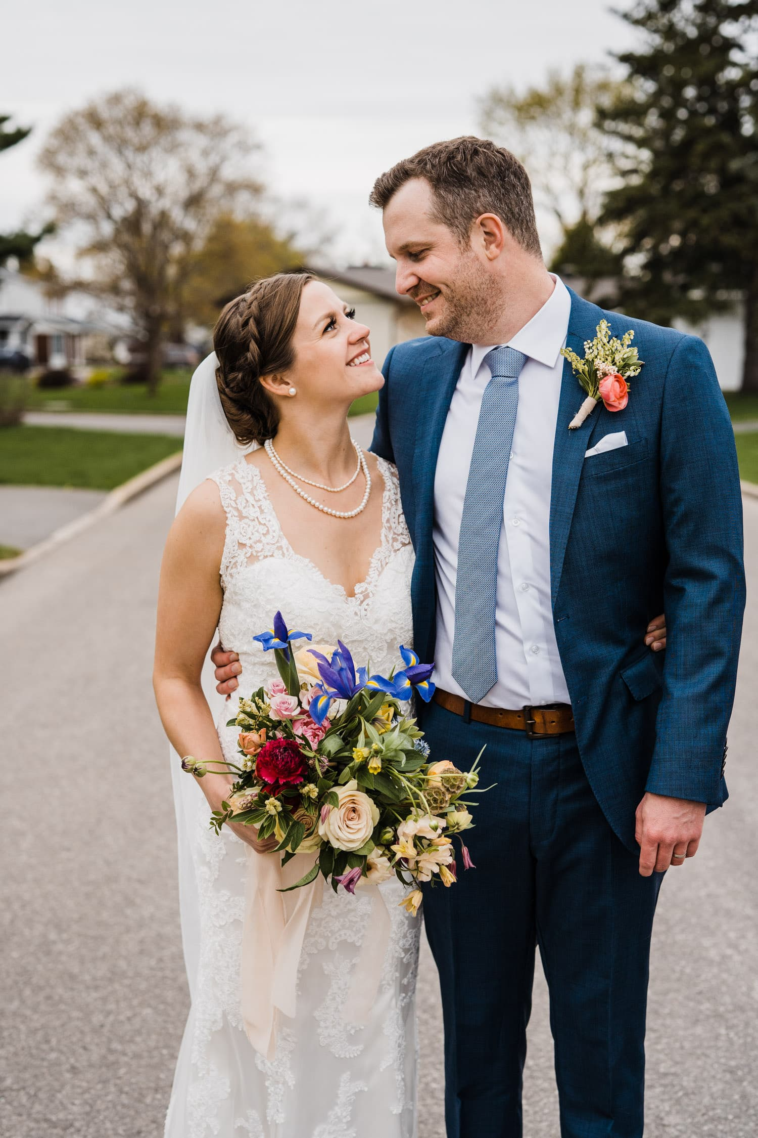 couple pose in the street after their backyard wedding ceremony