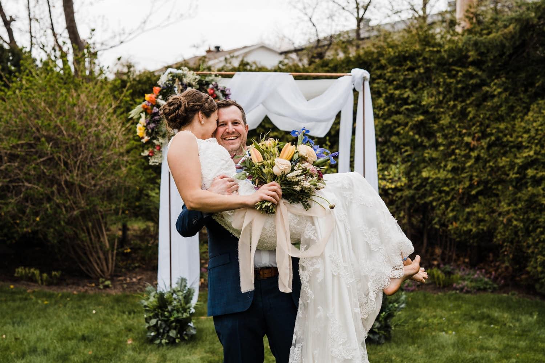 groom lifts bride up - small backyard wedding ottawa