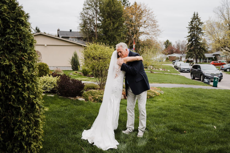 bride and her father hug ahead of small backyard wedding ottawa