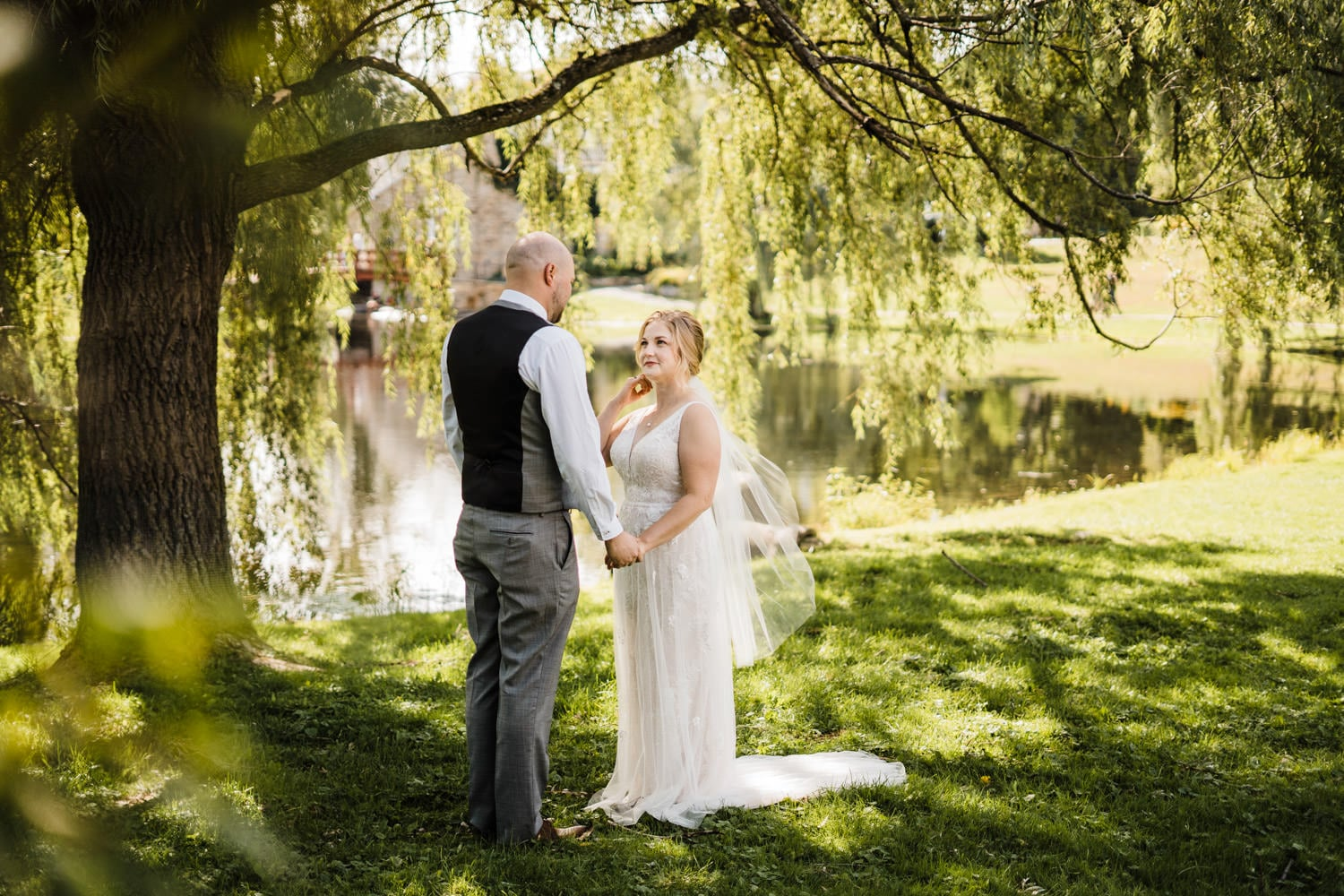 couple has their first look under willow tree in stewart park