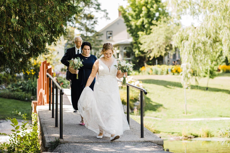 bride walks over bridge toward wedding ceremony