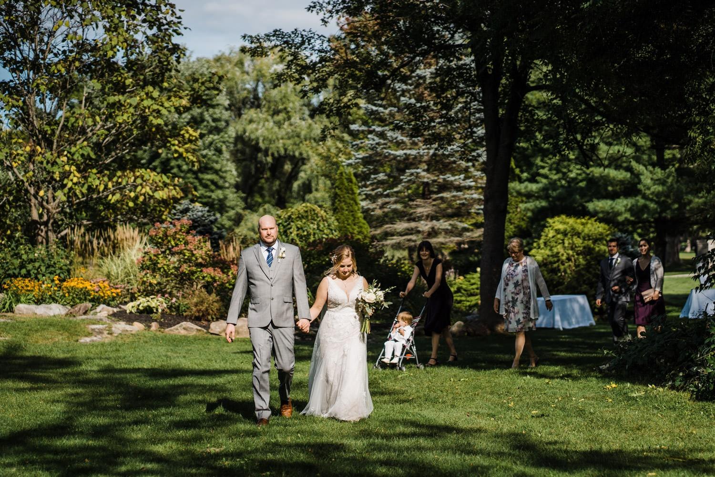 couple walk through Stewart Park together after wedding ceremony