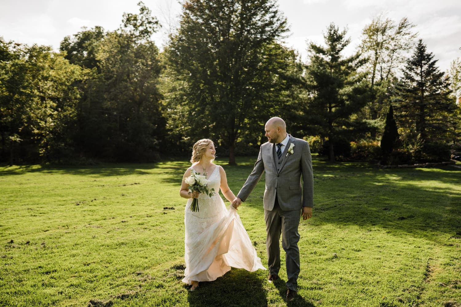 couple walk through park together after their wedding ceremony