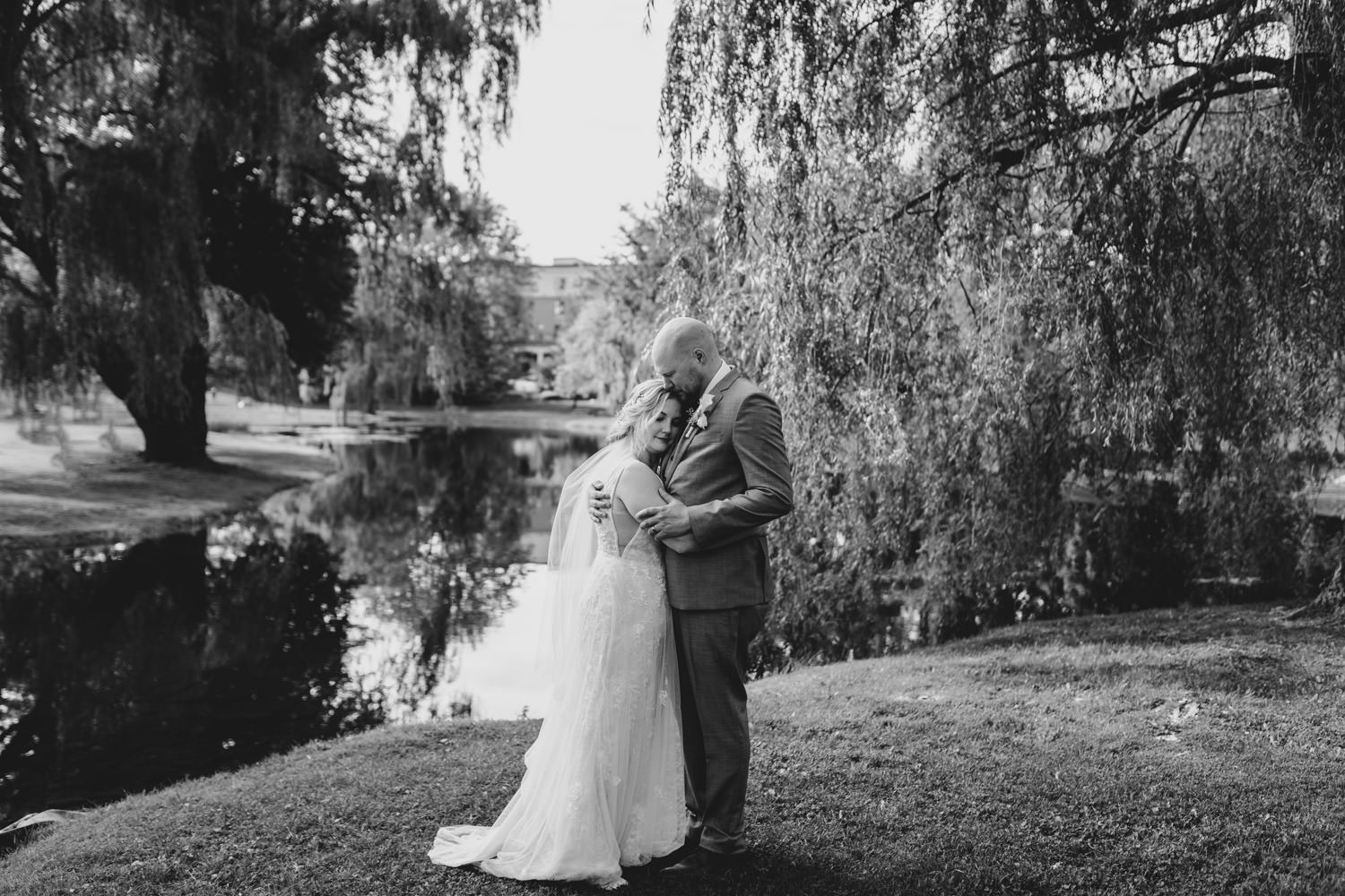 black and white portrait of bride and groom hugging next to pond in stewart park