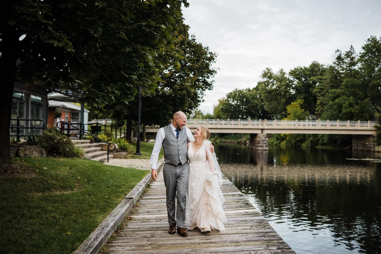 couple laugh and walk along dock - small stone cellar wedding perth