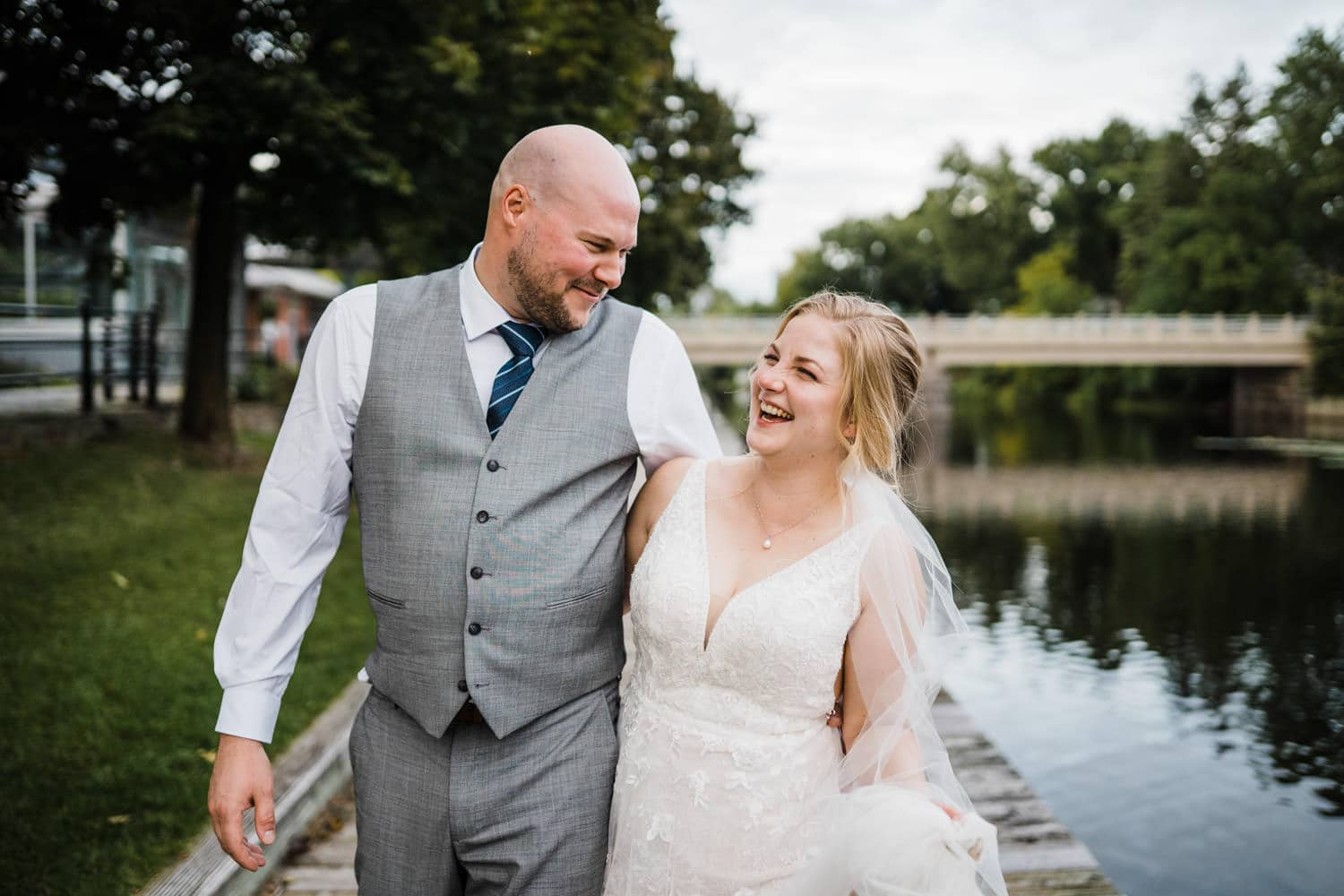 couple laugh together on dock next to river - small stone cellar wedding perth