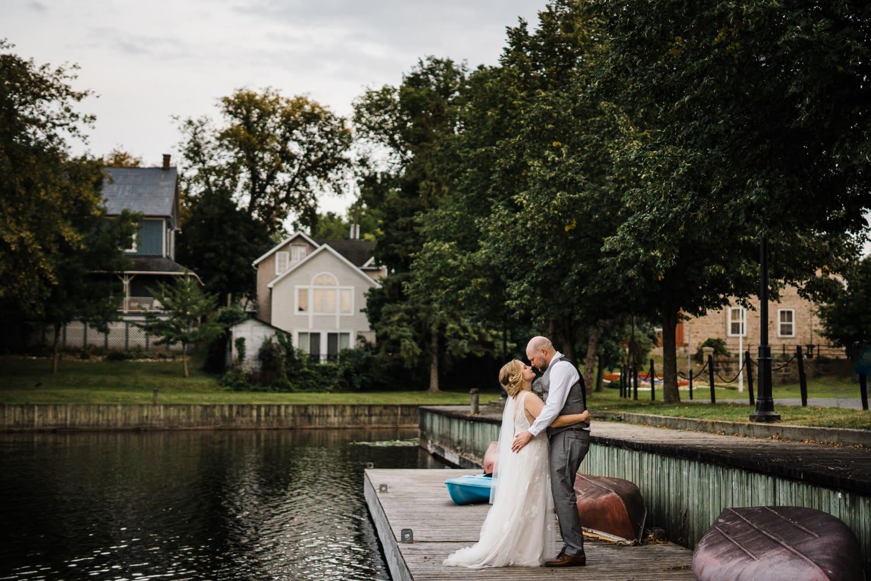 couple hug on a dock together - small stone cellar wedding perth