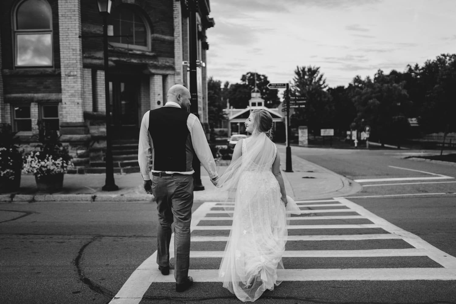 couple walk hand in hand across the street - stone cellar wedding in perth