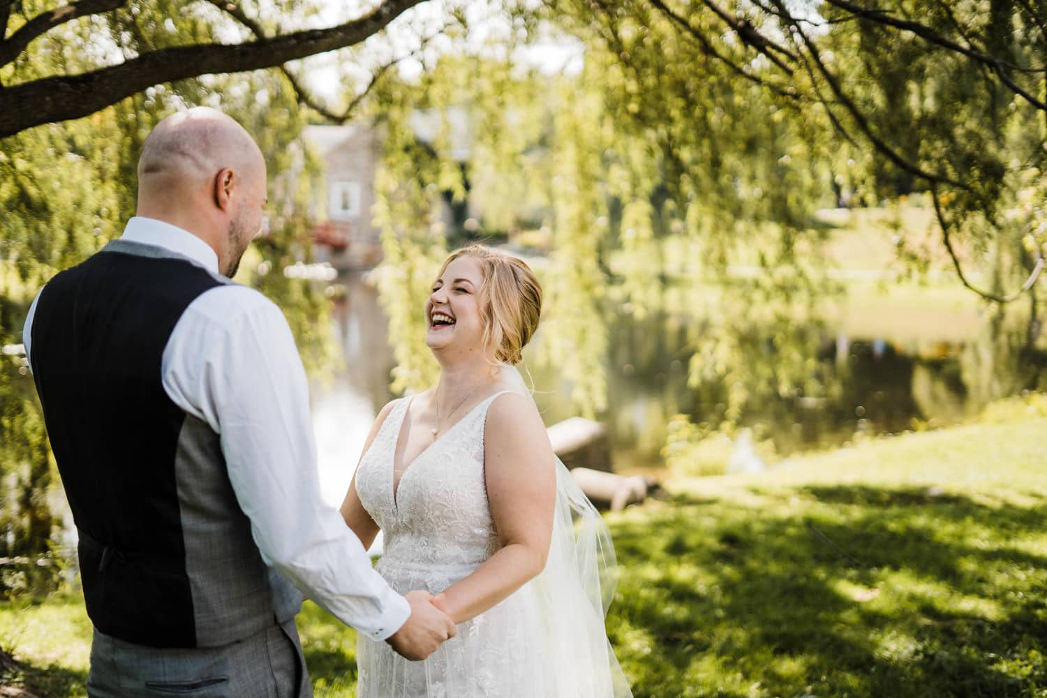 couple laugh during their first look in park